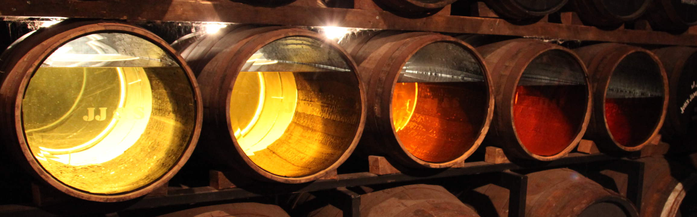 Barrels with aging whisky. Going from clear over yellow to a red wine colour
