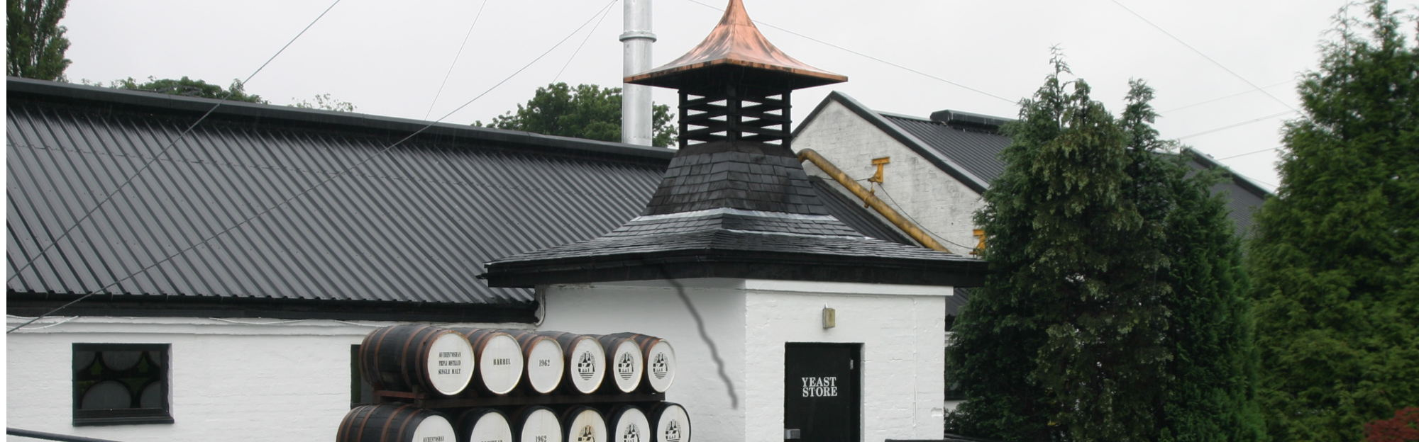 The Auchentoshan distillery with the barrels in front of the building with the kiln
