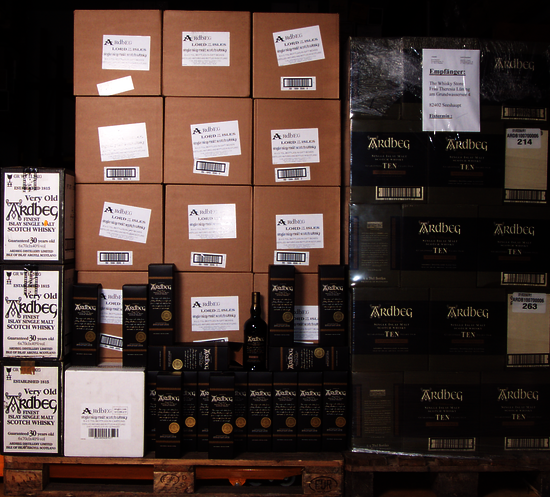 left pallet of ardbeg in brown boxes with a few bottles in front, right a pallet of Ardbeg TEN