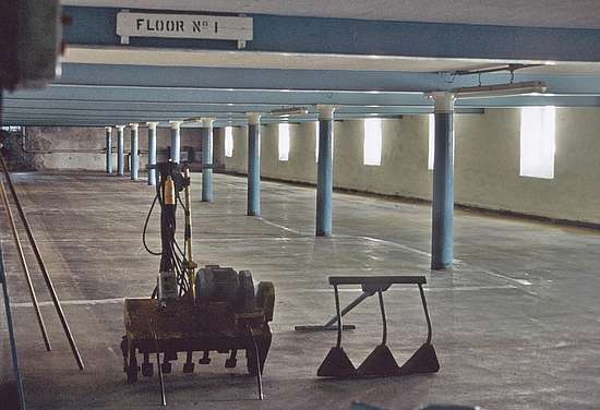 An empty malting floor and the barley spreader and a malt turner